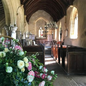 St Oswalds Church aisle with pink and white flowers in the foreground