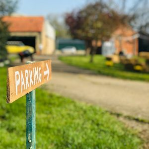 rustic parking sign made from wooden plank. background is blurred out